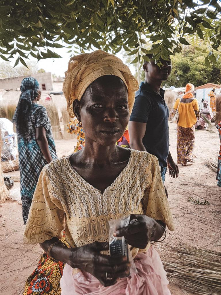 Et portrætbillede af en afrikansk kvinde der står på et marked´