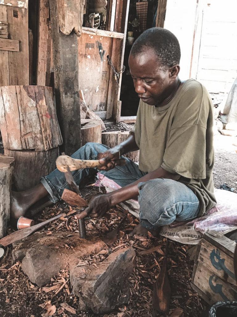 En træhugger der hugger træfigurer på jorden