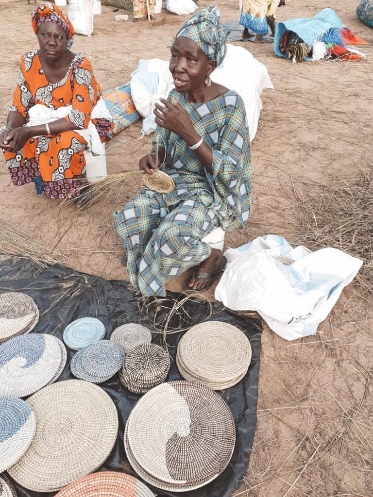 En afrikansk kvinde der sidder på jorden og fletter en sivkurv