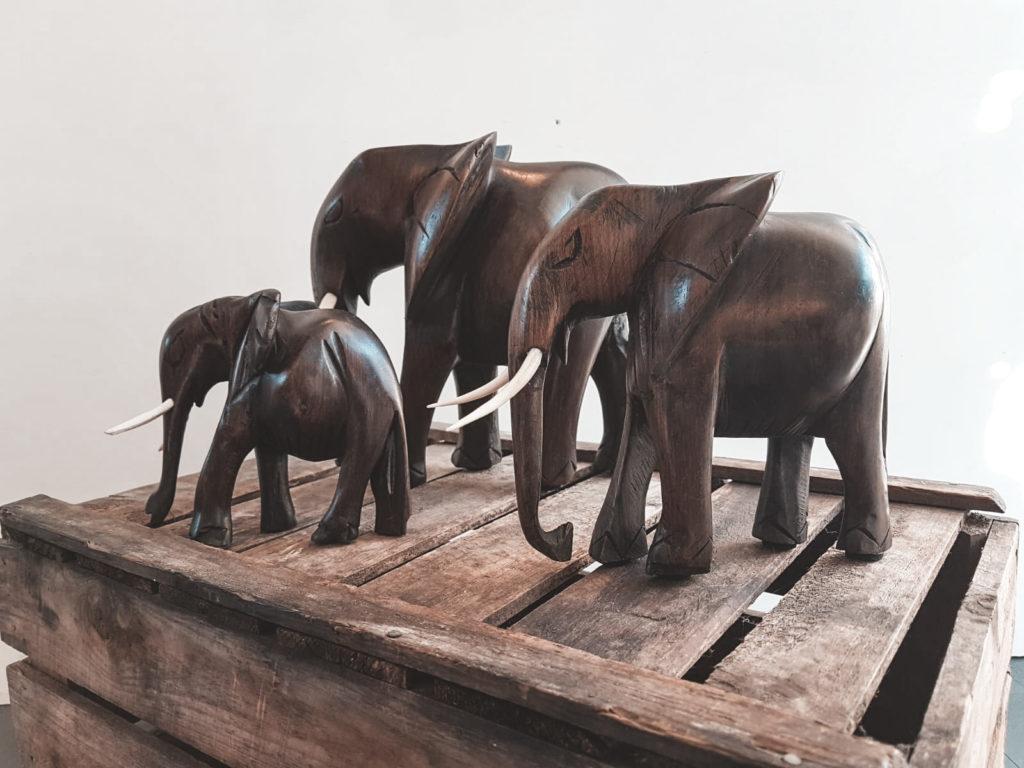 Tre træelefanter der står på en kasse