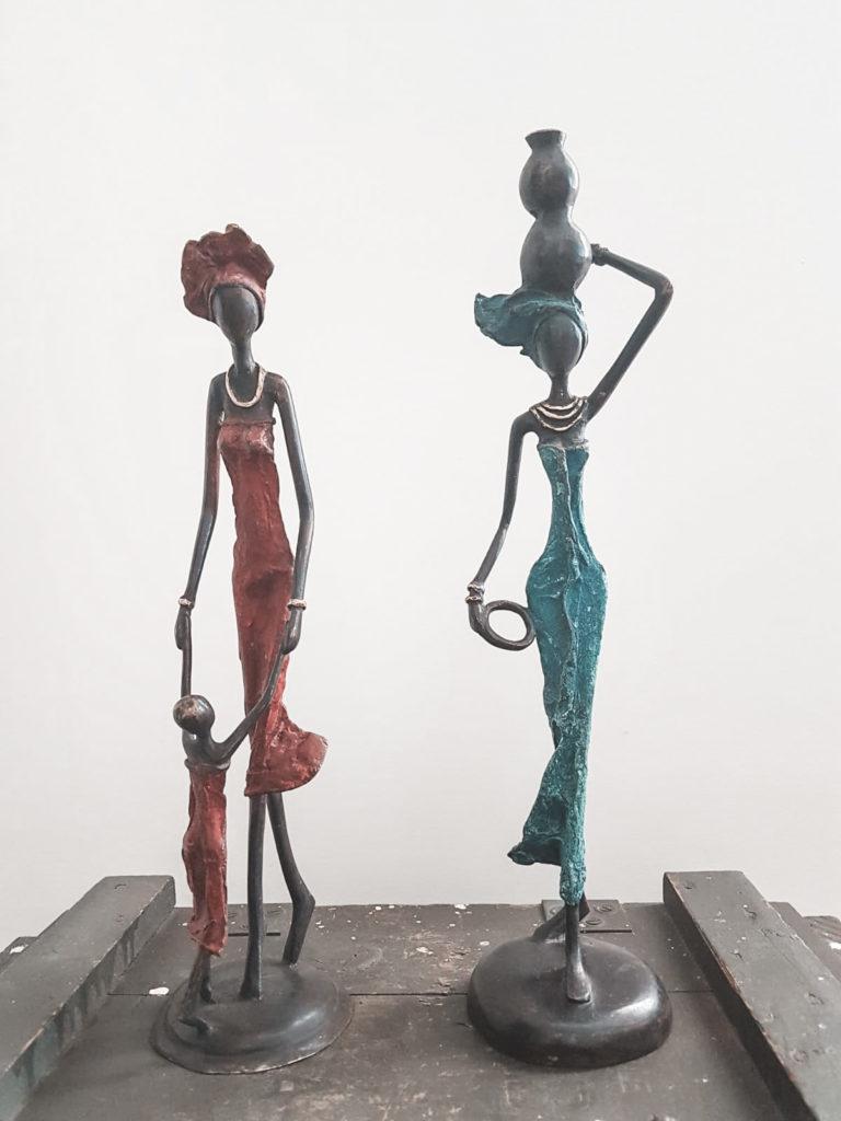 Tre messingfigurer af to kvinder og et barn der står på en trækasse