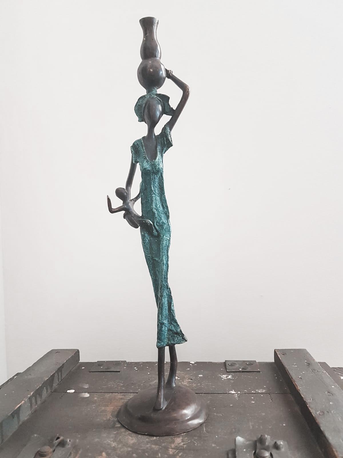 En messingfigur af en kvinde og et barm der står på en trækasse