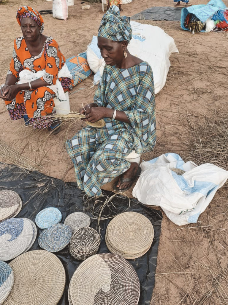 En afrikansk kvinde der fletter sivkurve mens hun sidder på jorden
