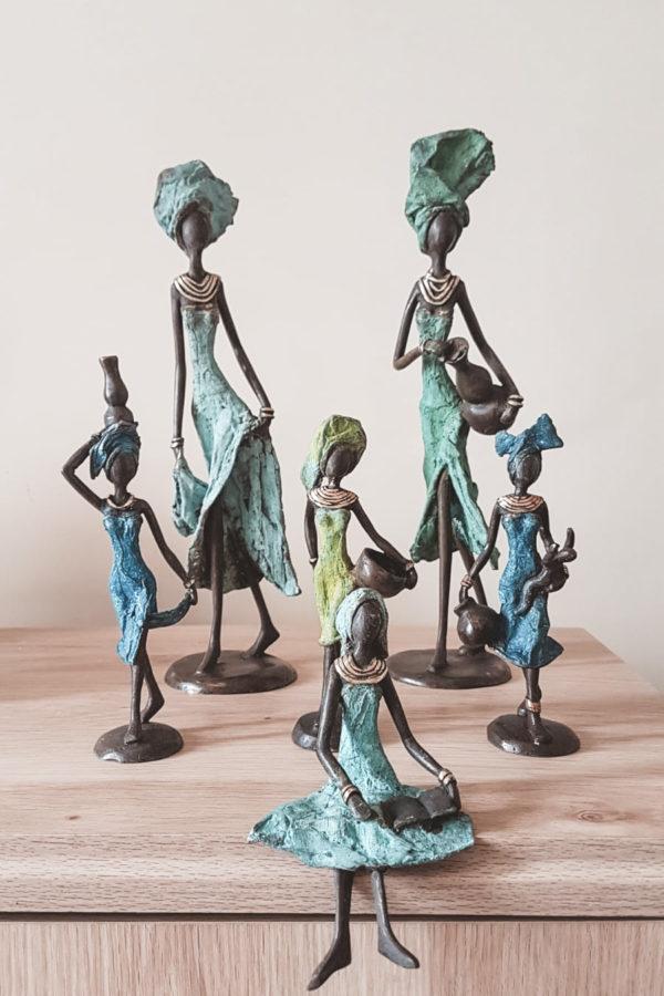 Forskellige messingfigurer af kvinde der står og sidder ned på en trækasse