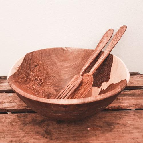 En salatskål lavet af træ med salatbestik der ligger i